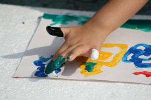 Child finger painting a yellow house and a blue cloud.